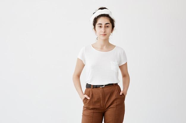 Bonita adolescente bonita veste camiseta branca solta e calça marrom, segura as mãos no bolso, sente prazer. menina de aparência agradável, posando contra parede branca