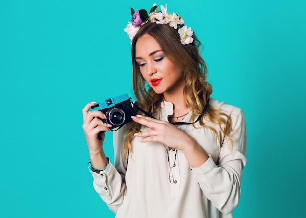 Bonita alegre loira mulher fresca com guirlanda floral na cabeça, posando em roupa elegante primavera, tirando foto em fundo azul brilhante. vestindo concurso grinalda floral, roupas de primavera.