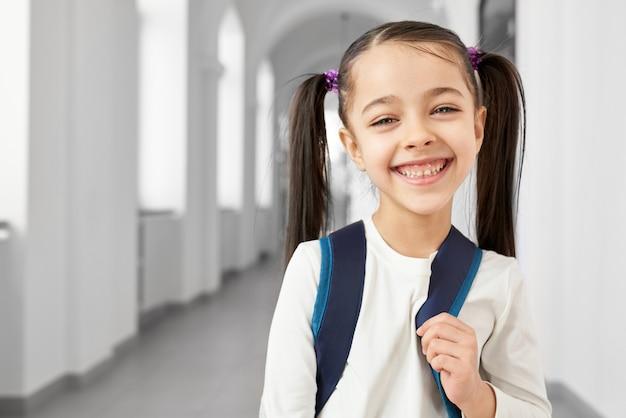 Bonita, bonita, feliz estudante com rabos de cabelo em pé no corredor longo, luz da escola primária sorrindo