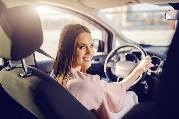Bonita caucasiana morena dirigindo o carro e olhando para a câmera. foto tirada do banco de trás.