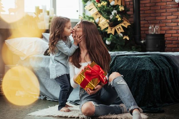 Bonita cena de beijo. mãe e filha senta-se no quarto decorado de férias e mantém a caixa de presente