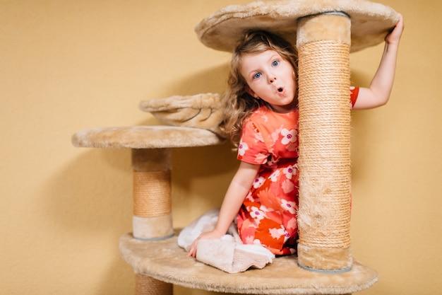 Bonita criança brinca com casa de gato grande e se alegra.