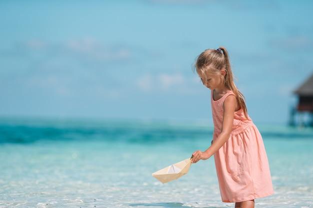 Bonita criança brincando com barquinhos de papel em um mar