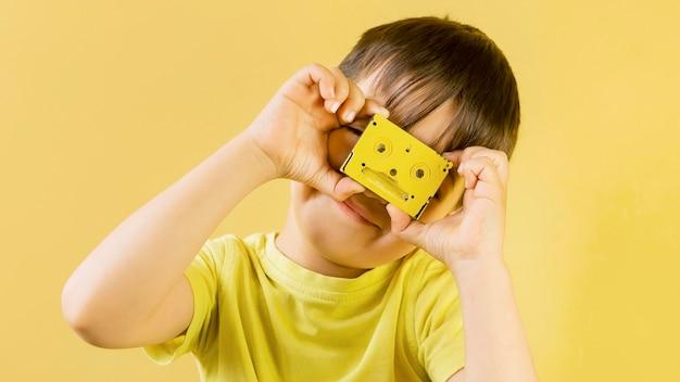 Bonita criança brincando com uma fita cassete antiga