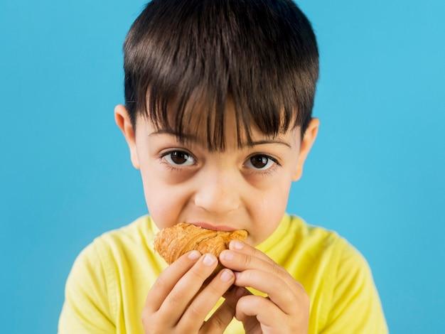 Bonita criança comendo um croissant