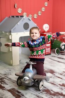 Bonita criança está brincando com carros de brinquedo vermelho