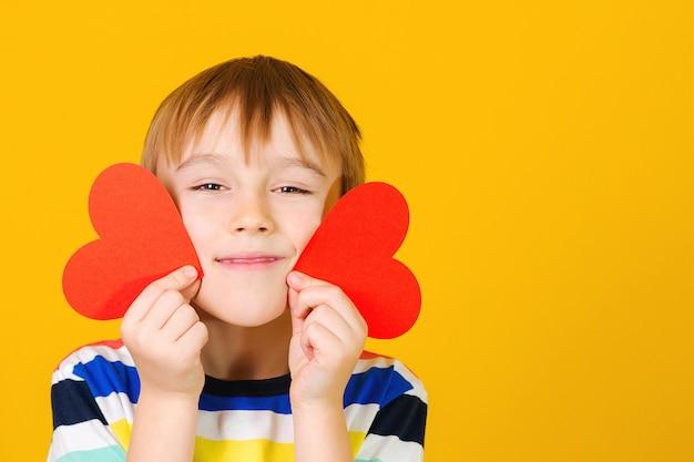 Bonita criança segurando cartas de corações vermelhos. menino sorridente com cartão de cumprimentos.