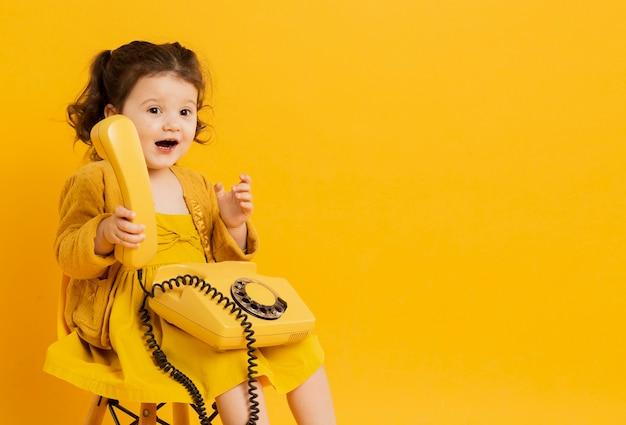 Bonita criança segurando o telefone enquanto posava