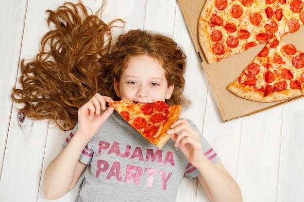 Bonita criança segurando uma fatias de pizza, deitado no chão de madeira