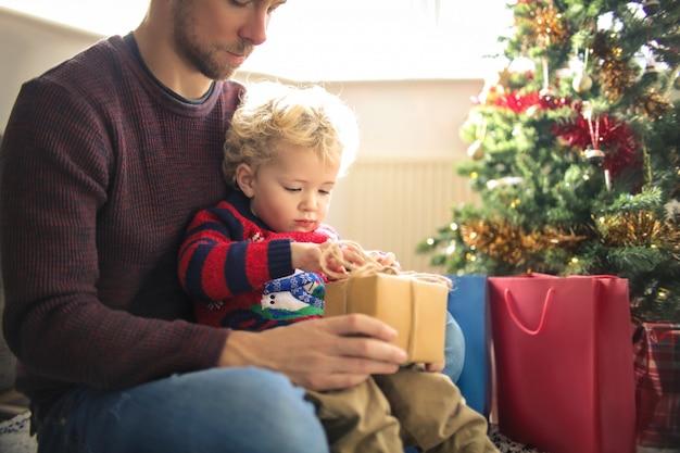 Bonita criança sentada na perna do pai, abrindo um presente de natal