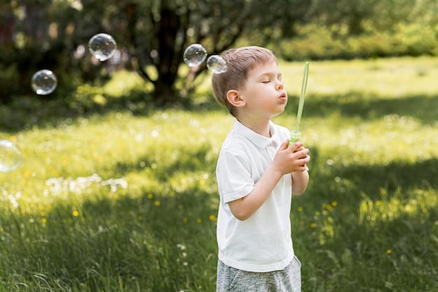 Bonita criança soprando bolhas com seu brinquedo