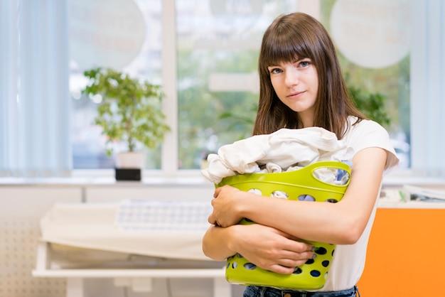 Bonita dama segurando o cesto de roupa suja