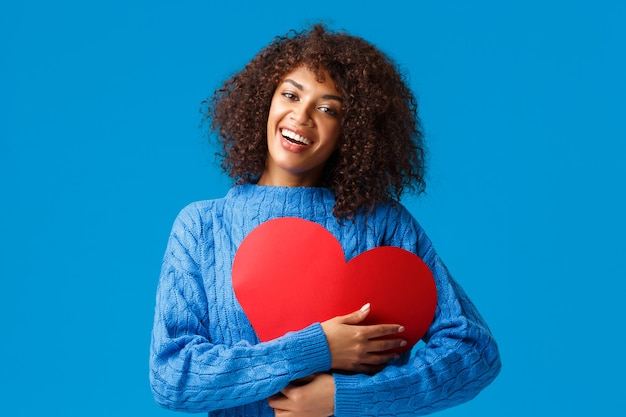 Bonita e carinhosa engraçada, sorridente mulher afro-americana com corte de cabelo afro, pressione o grande sinal de coração vermelho no peito e abrace-o com um sorriso encantador encantado, mostrando amor e carinho, parede azul.