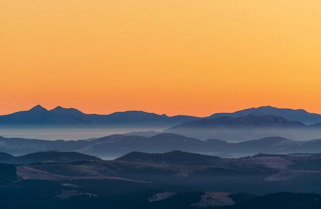 Bonita e colorida paisagem montanhosa em tons de laranja e azuis com névoa matinal ao nascer do sol.