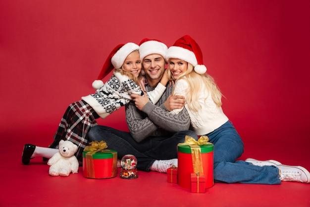 Bonita e jovem família feliz usando chapéus de natal sentado isolado