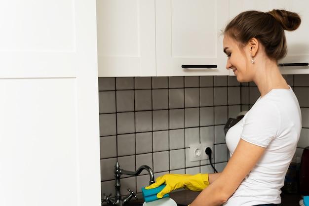 Bonita e jovem garota lava a louça na pia. o conceito de limpeza de primavera e empresa de limpeza. mulher lavando os pratos na pia da cozinha no restaurante