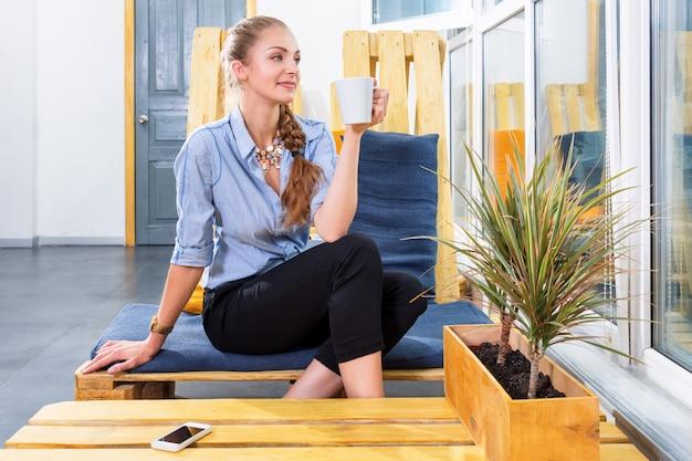 Bonita empresária bebendo café quente da manhã e sonhando em loft moderno. mulher de negócios. freelancer no centro de coworking está descansando e saboreando a bebida. conceito de trabalho freelance.