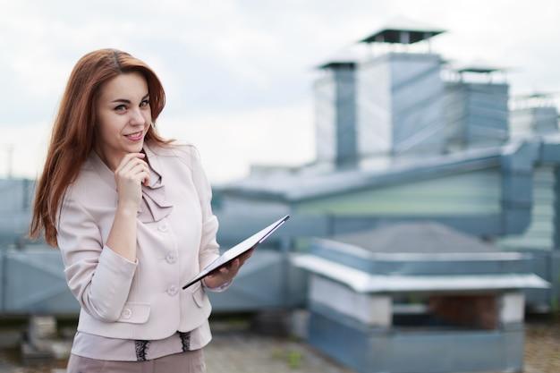 Bonita empresária em terno bege ficar no telhado e segurar o tablet vazio