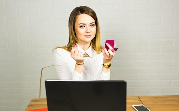 Bonita empresária fazendo maquiagem no escritório
