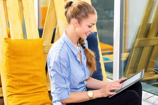Bonita empresária trabalhando com novo projeto de inicialização usando o tablet no apartamento moderno. mulher de negócios.