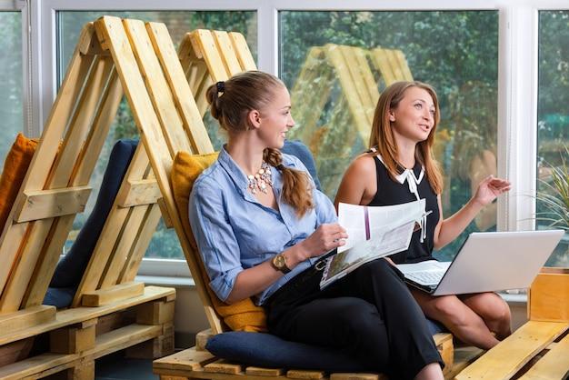 Bonita empresária trabalhando em conjunto com o novo projeto de inicialização usando o laptop no apartamento moderno. conceito dos povos e dos trabalhos de equipa - equipe criativa feliz no escritório. mulheres em negócios.