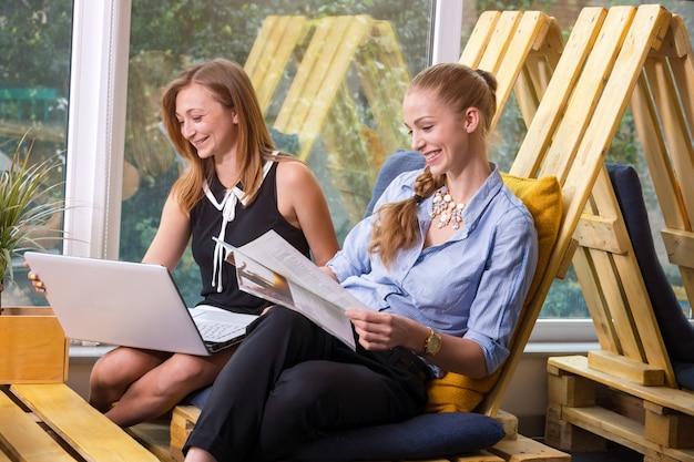 Bonita empresária trabalhando em conjunto com o novo projeto de inicialização usando o laptop no apartamento moderno Foto Premium