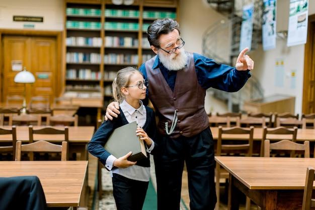 Bonita estudante adolescente segurando um livro grande e ouvindo seu avô barbudo sênior inteligente ou homem bibliotecário