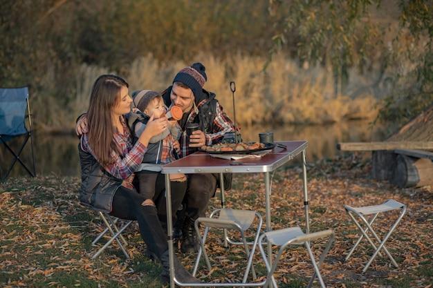 Bonita família sentada em um piquenique em uma floresta