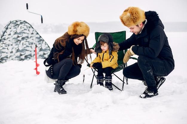 Bonita família sentada em uma pesca de inverno com o filho pequeno