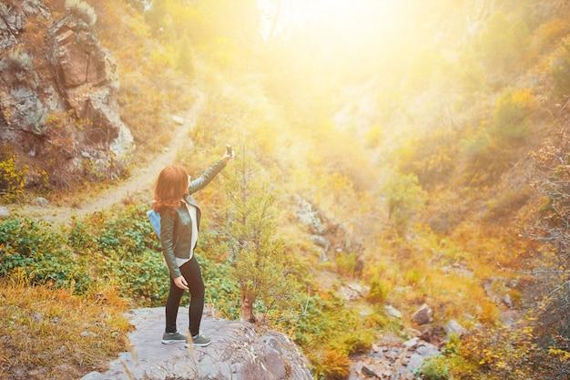 Bonita feminina caminhante tomando selfie ou fazendo vídeo ao vivo transmitir vlog na floresta de montanhas