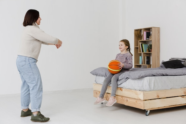 Bonita filha segurando basquete dentro de casa