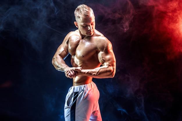 Bonita fisiculturista forte posando na parede de fumaça