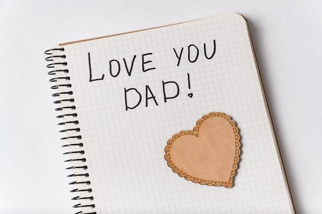 Bonita inscrição no caderno eu te amo pai. bloco de notas e coração de close-up