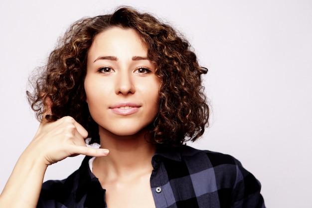 Bonita jovem atraente segurando a mão perto da chamada de orelha