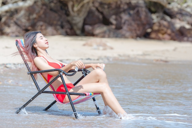 Bonita jovem mulher asiática em biquíni feliz na bela praia nas férias de verão na tailândia