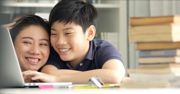 Bonita mãe asiática ajudando seu filho a fazer sua lição de casa.