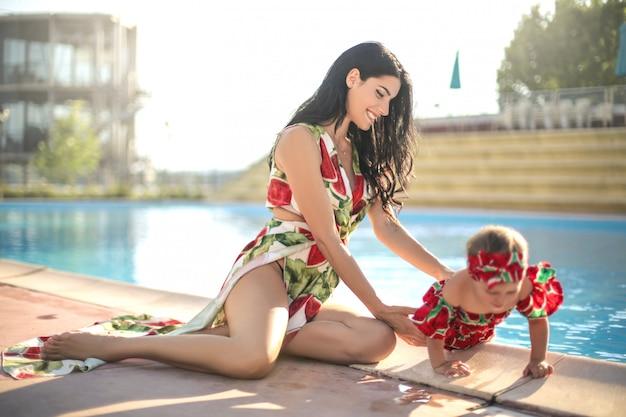 Bonita mãe brincando com a filha ao lado de uma piscina