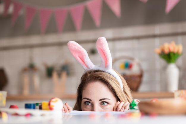 Bonita mãe com orelhas de coelho se escondendo
