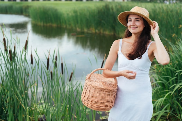 Bonita mãe posando à beira do lago com uma cesta de piquenique
