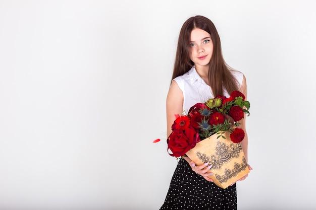 Bonita menina adolescente morena segurando grande boquet de flores vermelhas