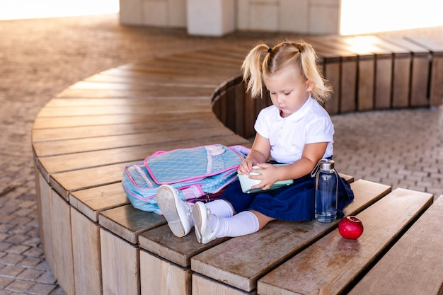 Bonita menininha sorridente segurando um hambúrguer e suco de laranja ao ar livre