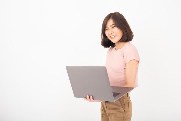 Bonita mulher adolescente asiática está trabalhando com o computador na parede branca