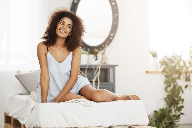 Bonita mulher africana macia em roupa de noite, sentado na cama em casa, sorrindo, sonhando, pensando em seu apartamento espaçoso.
