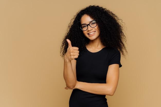 Bonita mulher afro-americana satisfeita mantém o polegar para cima, vestida com camiseta preta casual, tem cabelos nítidos