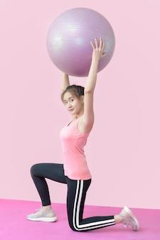Bonita mulher asiática fazendo exercícios de ginástica com bolas.