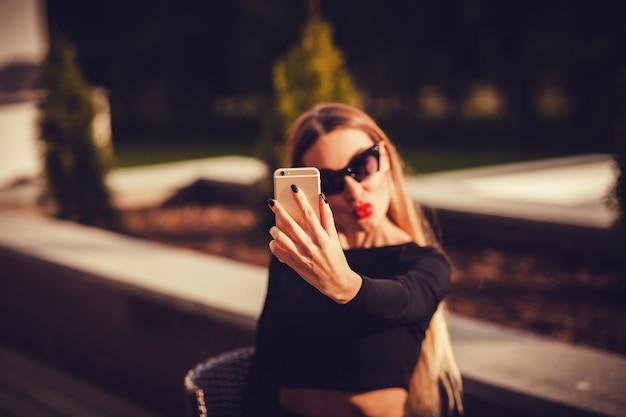 Bonita mulher caucasiana tomando uma selfie com smartphone