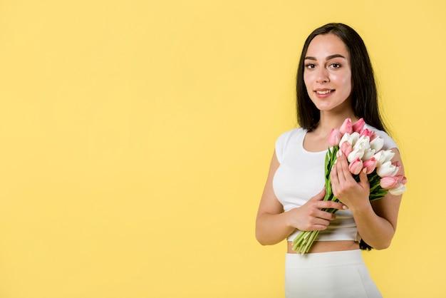 Bonita mulher com tulipas brancas e rosa