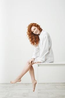 Bonita mulher concurso bonita com cabelo ruivo cacheado rindo posando sentado na mesa. copie o espaço.