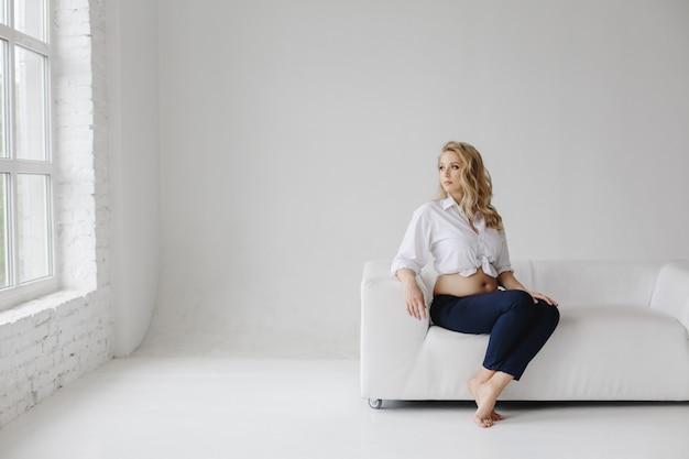 Bonita mulher grávida senta-se no sofá e olha pela janela