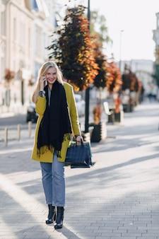 Bonita mulher loira atraente com pacotes na rua em tempo ensolarado. comunica ao telefone depois das compras, emoções positivas.